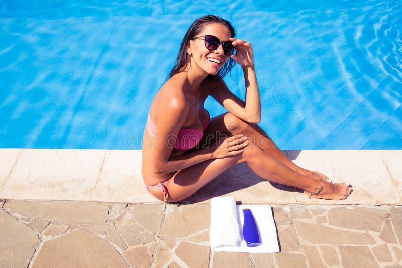 晒日光浴在游泳水池附近的快乐的妇女 免版税库存照片