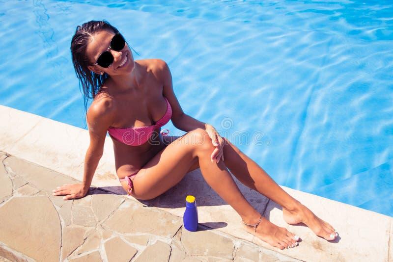晒日光浴在游泳水池附近的愉快的妇女 图库摄影