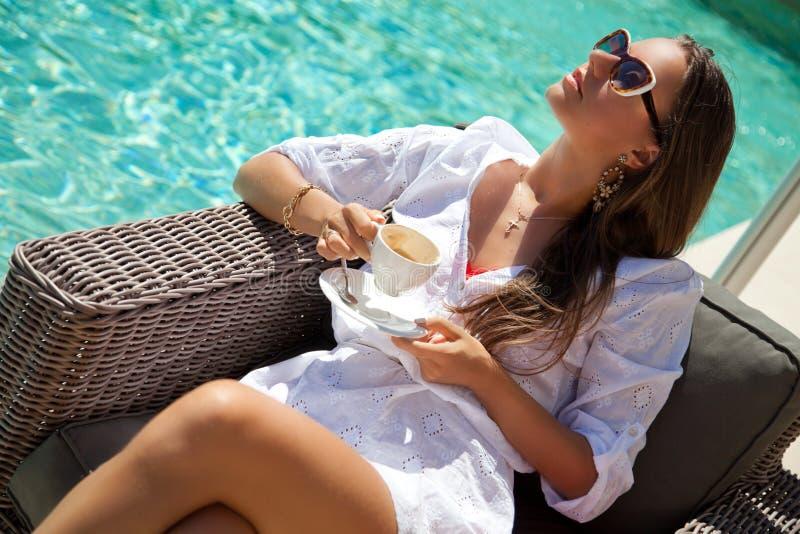 晒日光浴在躺椅游泳池边的愉快的少妇 免版税库存图片
