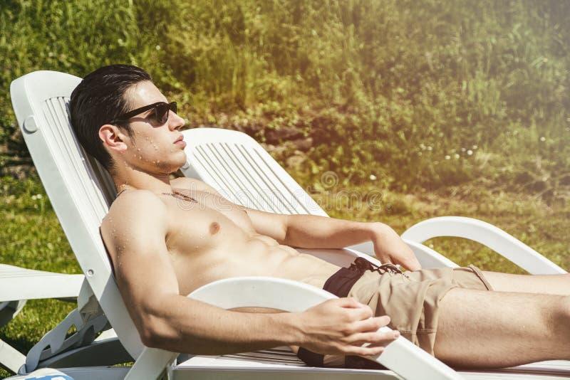 晒日光浴在躺椅的赤裸上身的年轻人  库存照片