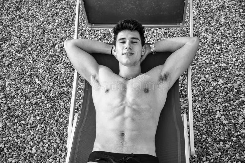 晒日光浴在躺椅的赤裸上身的年轻人  图库摄影