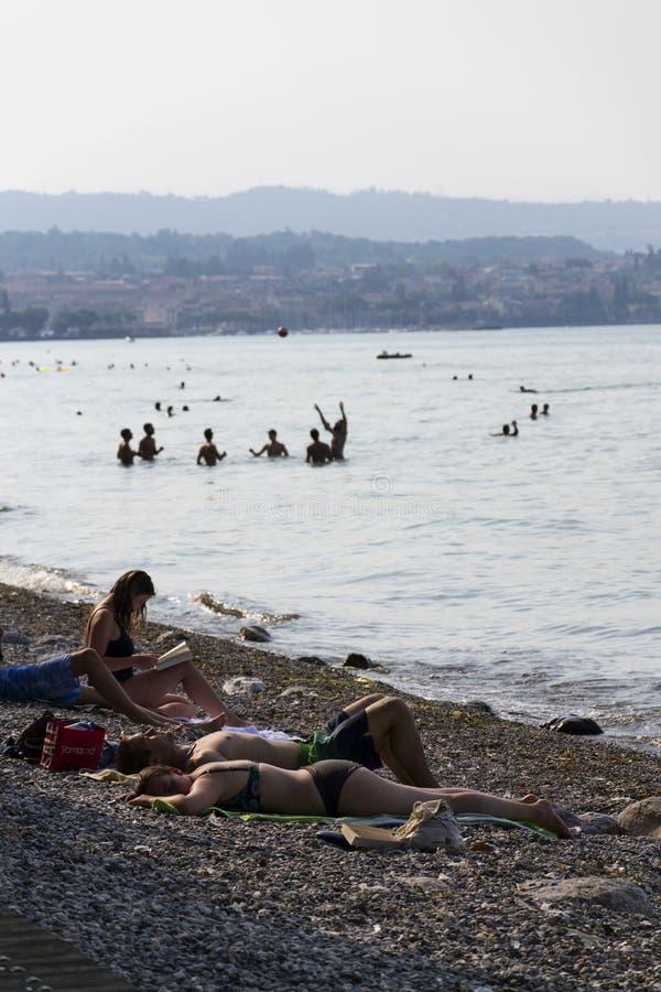 晒日光浴在2016年7月30日的海滩的人们在Desenzano del加尔达,意大利 免版税图库摄影