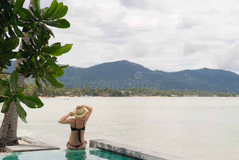 晒日光浴在水池附近的妇女 库存照片
