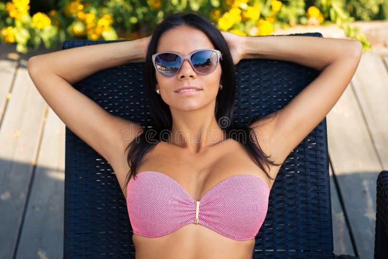 晒日光浴在deckchair的可爱的妇女 库存照片