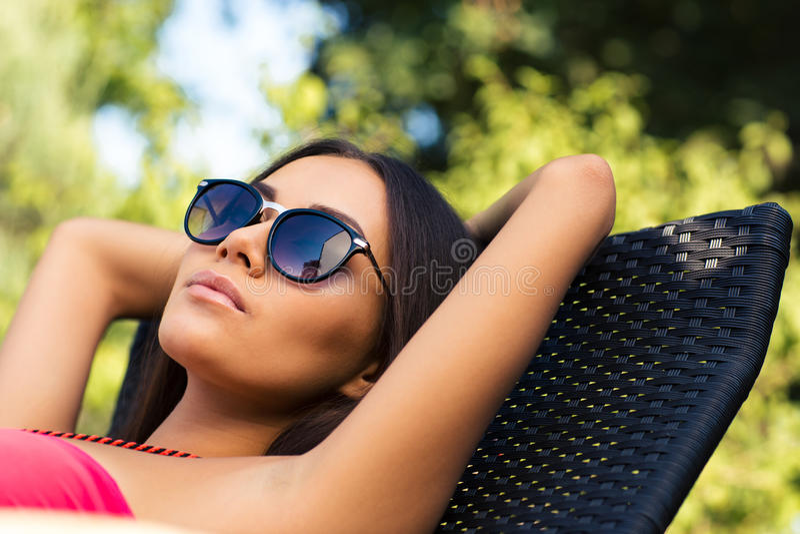 晒日光浴在deckchair的妇女 图库摄影