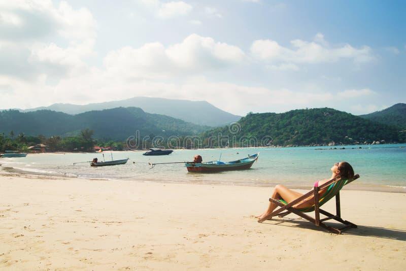 晒日光浴在deckchair的美丽,适合的妇女 免版税图库摄影