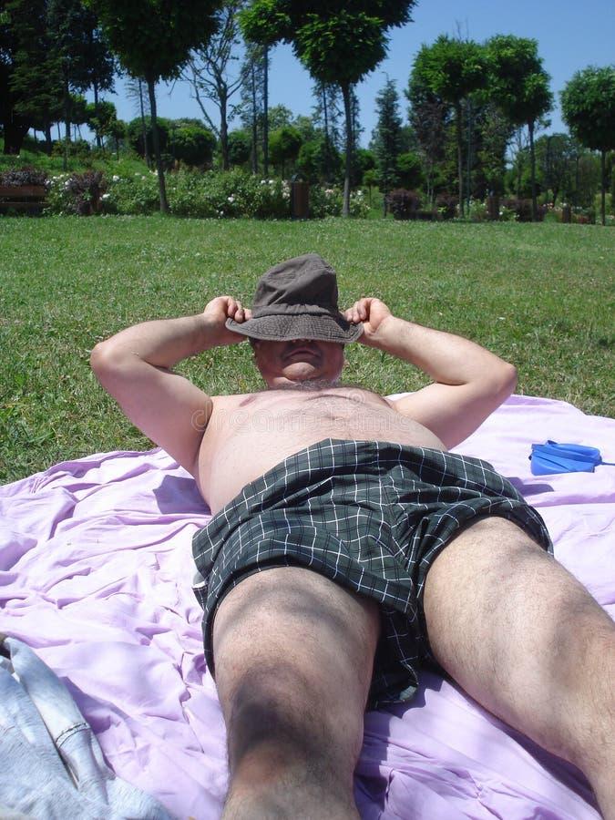 晒日光浴的人,投入在他的帽子 免版税库存图片