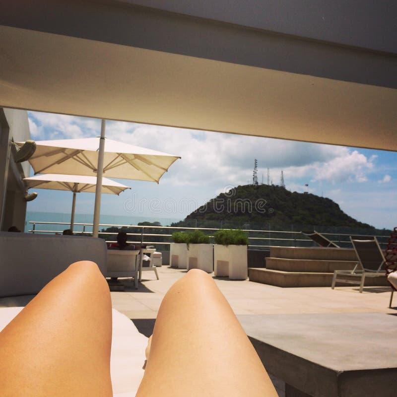晒日光浴的屋顶夏天比基尼泳装晴朗的游泳池边 免版税库存照片
