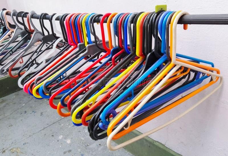 晒衣架或勾子垂悬的穿衣与多种颜色 免版税图库摄影
