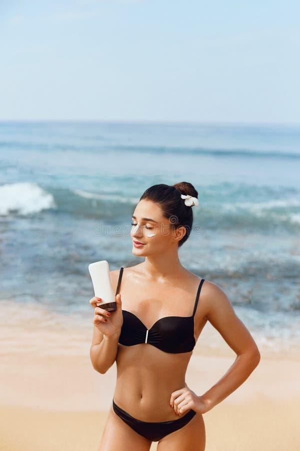 晒黑化妆水 应用在海滩的性感的年轻女人遮光剂太阳奶油 r r r ??hol 免版税库存照片