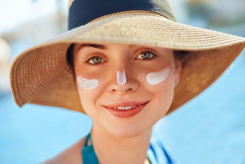 晒黑应用遮光剂的化妆水妇女 在面孔的女性污迹防晒霜 Skincare 库存照片