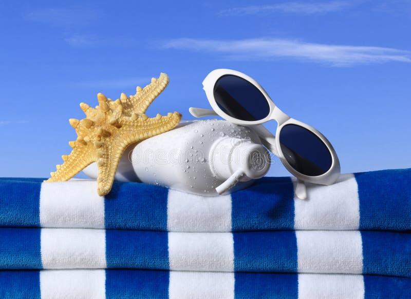 晒黑化妆水海滩毛巾太阳镜 免版税图库摄影