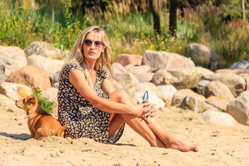 晒黑和放松在海滩的愉快的妇女太阳 免版税图库摄影
