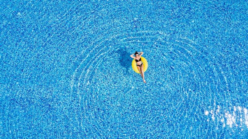 晒黑在池 妇女在水池放松在黄色可膨胀的圆环的晴天 库存图片