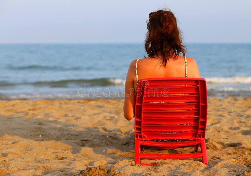 晒黑在海滨的妇女在日落 免版税库存图片