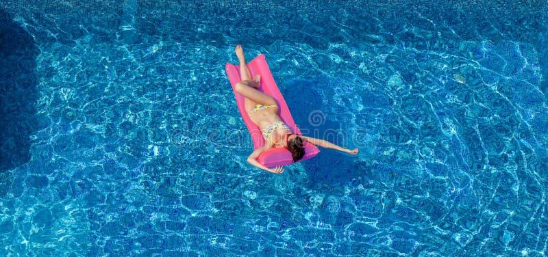 晒黑在游泳池的桃红色床垫的性感的深色的妇女 库存图片