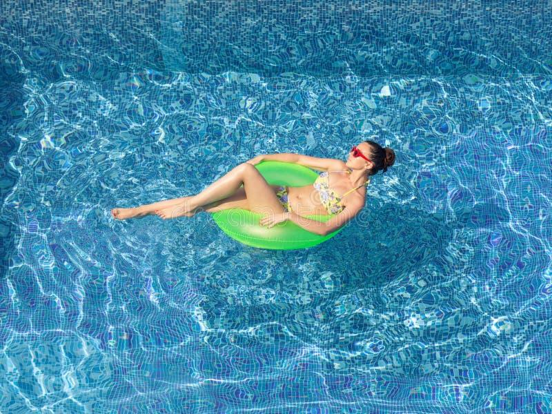 晒黑在游泳poo的可膨胀的圈子的性感的深色的妇女 免版税库存图片