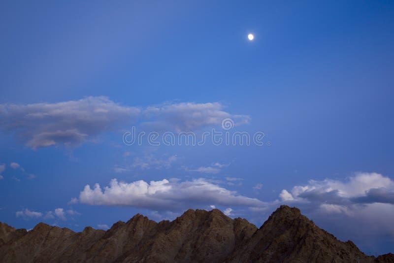 晚上、夜深蓝天空与云彩与星和月亮在沙漠山 库存图片
