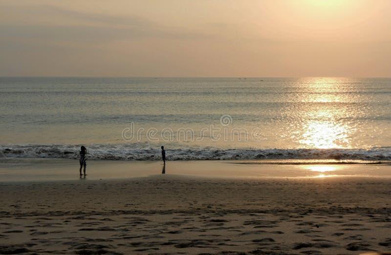 晚上太阳和游人金黄海滩的在库塔使巴厘岛印度尼西亚靠岸 免版税图库摄影
