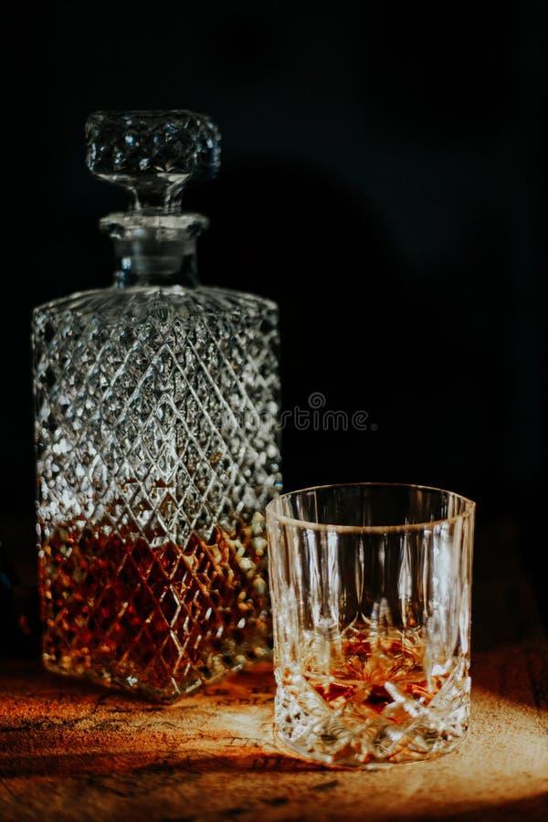 晚上威士忌酒杯和酒瓶 免版税库存图片