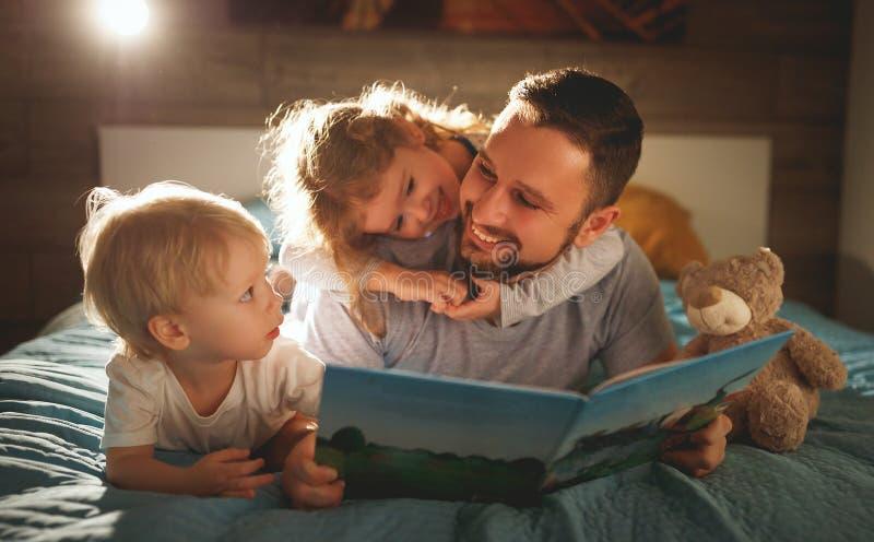 晚上家庭读书 父亲读孩子 在goin前的书 免版税图库摄影
