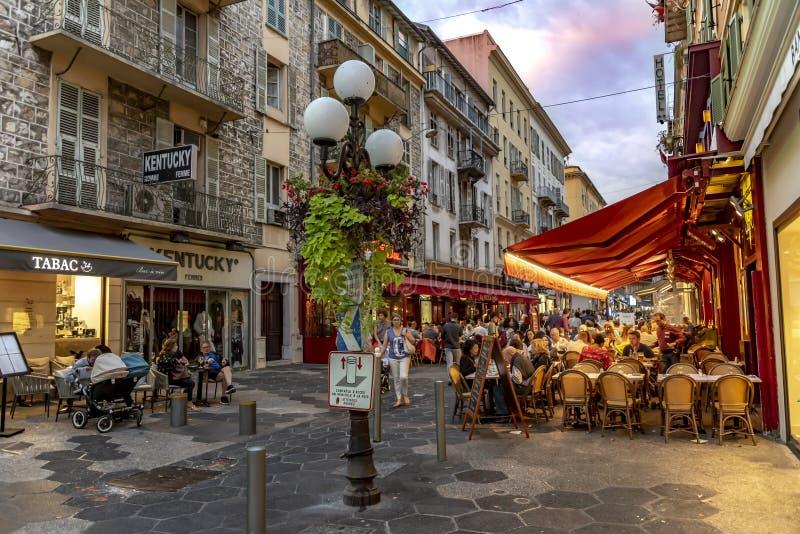 晚上被射击商店和一家餐馆有桌、椅子和人的一条街道的边路的在尼斯,法国 免版税库存照片