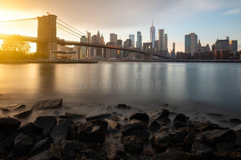 晚上East河在纽约 布鲁克林大桥和曼哈顿下城看法在日落期间 免版税库存照片