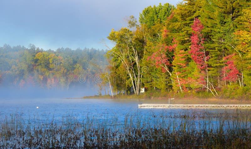 晚夏太阳在从湖上升的早晨有薄雾的雾发光 船坞延伸到从岸的一个湖 免版税库存图片