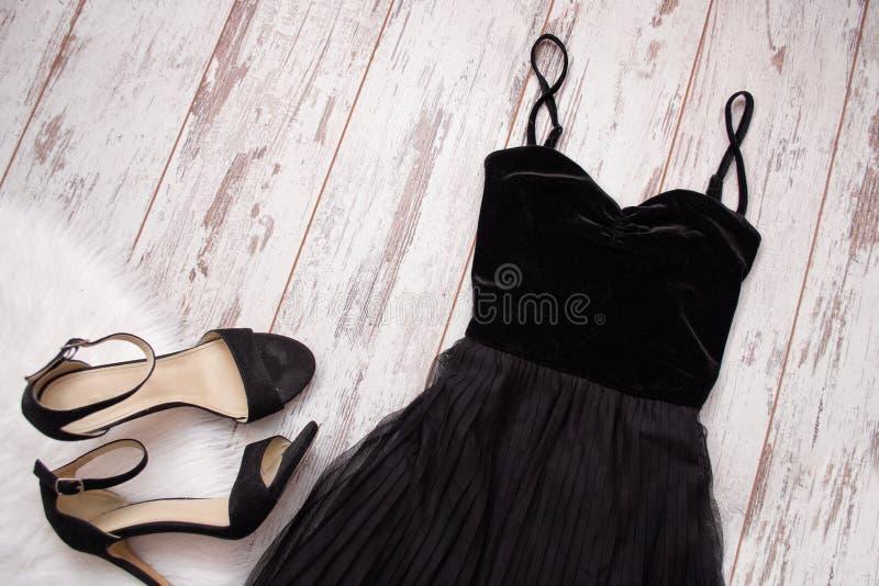 黑晚礼服和鞋子在木背景 秀丽蓝色聪慧的概念表面方式构成妇女 顶视图 库存图片