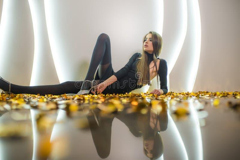 晚礼服的年轻女人在与金黄五彩纸屑的地板上 库存图片