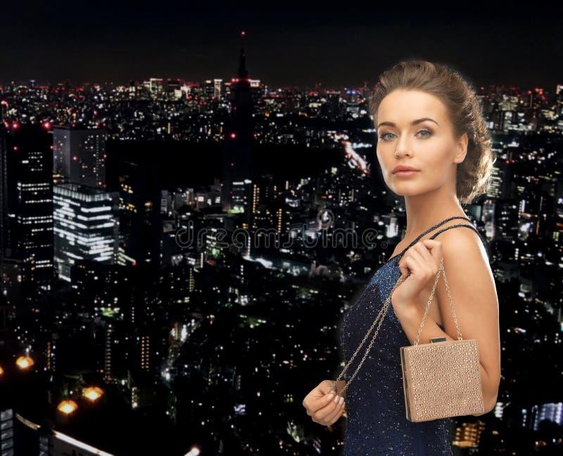 晚礼服的愉快的妇女与小袋子 图库摄影