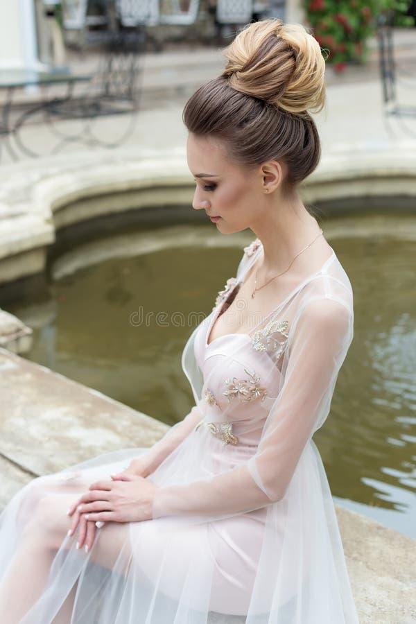 晚礼服的美丽的典雅的女孩与美好的在喷泉附近的晚上欢乐发型 库存照片