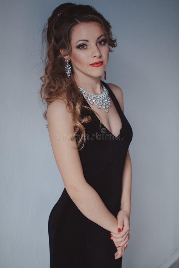黑晚礼服鸡尾酒会的美丽的女孩 免版税库存图片