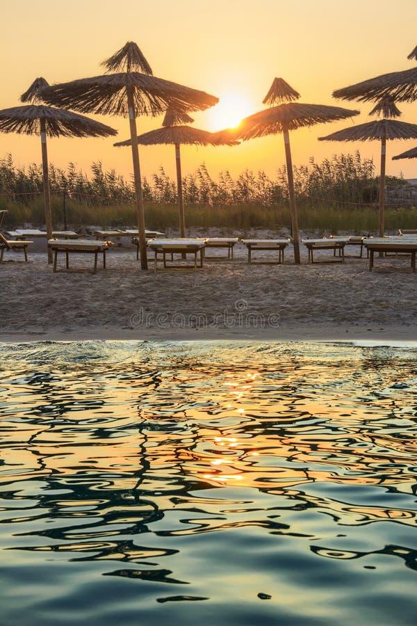 普利亚最美丽的沙滩  Torre Guaceto :在日落的伞 它是海洋的保护与8的区域和自然保护 库存照片