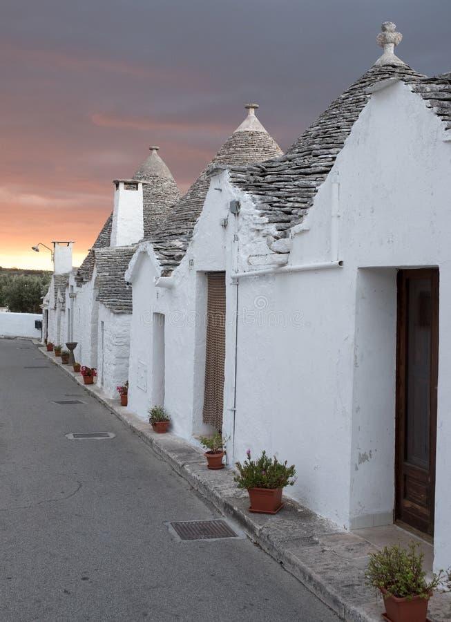普利亚,意大利 在一条街道上的传统圆锥形被顶房顶的trulli房子在阿尔贝罗贝洛 与红色天空的被拍摄的清早 库存照片