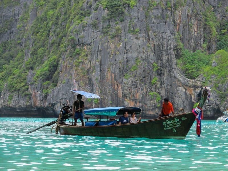 普吉岛,普吉岛泰国- 10 15 2012年:木小船由泰国人负责航行与沿美丽的两三个外国游人 免版税库存图片