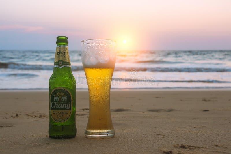 普吉岛,泰国-小店12日2019年:misted瓶和杯在海滩的冷的张啤酒在海景背景,日落天空 免版税库存照片