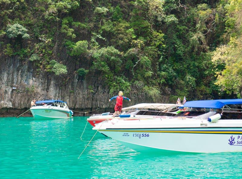 普吉岛,泰国- 2019年3月27日:一个游泳衣和游泳的风镜跃迁的一个小男孩从一条小船到水里 免版税库存图片