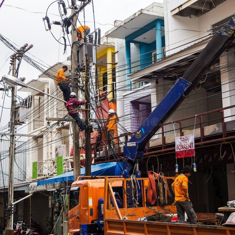 普吉岛,泰国- 2017年3月22日:输电线定象 电工与高压导线一起使用 免版税库存照片