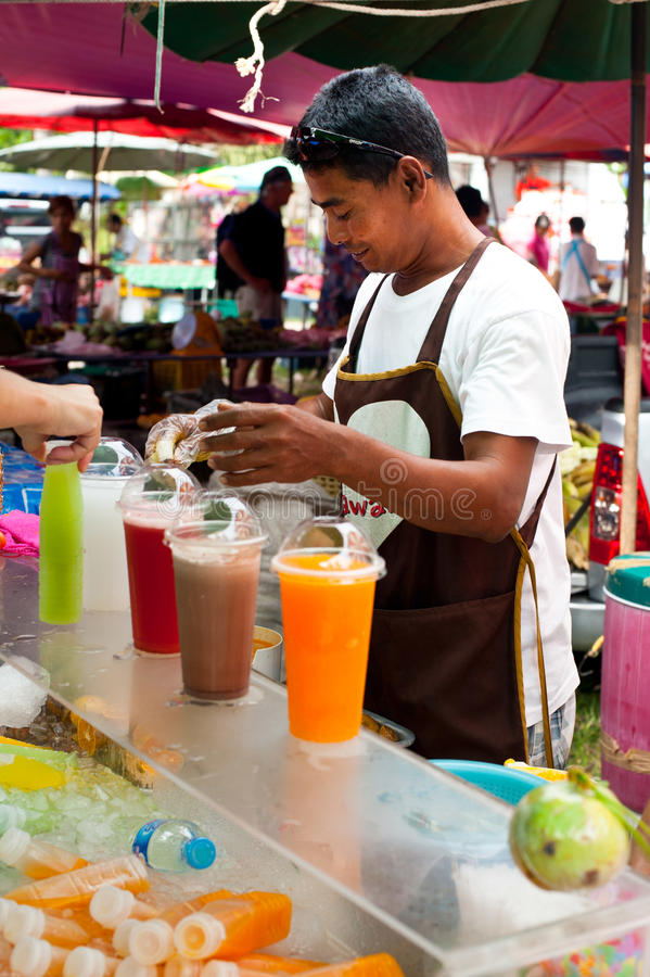 卖新鲜的汁液的泰国人在市场上 库存图片