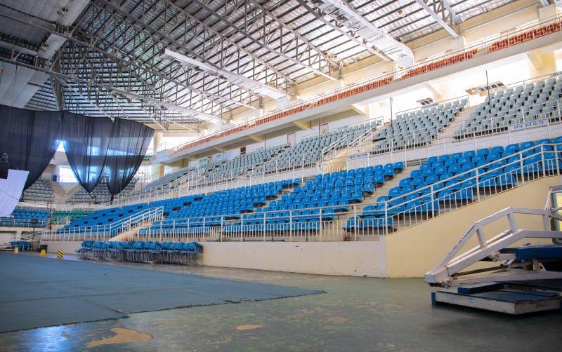普埃尔托普琳塞莎,菲律宾- 2018年11月27日:有塑料椅子和阶段的空的体育场 体育大剧场大厦 免版税库存图片