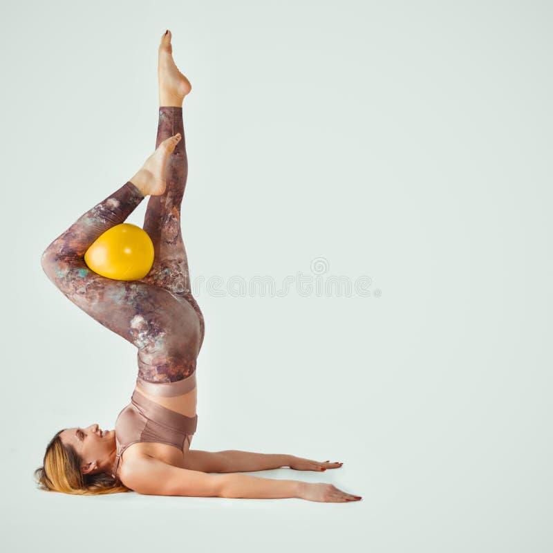普拉提 做与球的美丽的妇女锻炼 在肩胛骨的机架 库存照片