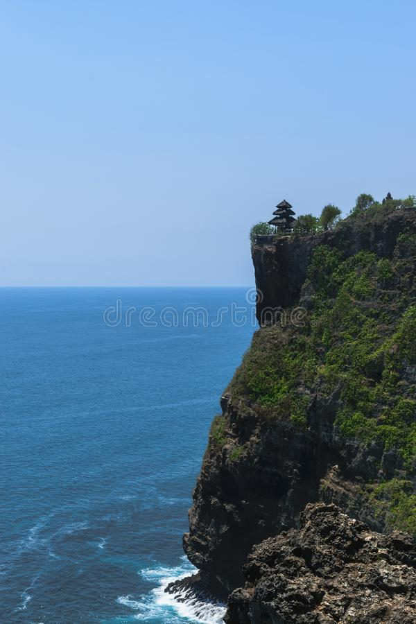普拉luhur在峭壁的uluwatu寺庙有蓝色印度洋美丽的景色在巴厘岛,印度尼西亚 库存照片