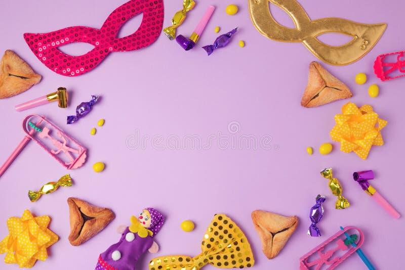 普珥节与狂欢节面具、hamans耳朵曲奇饼和党供应的假日概念在紫色背景 库存照片