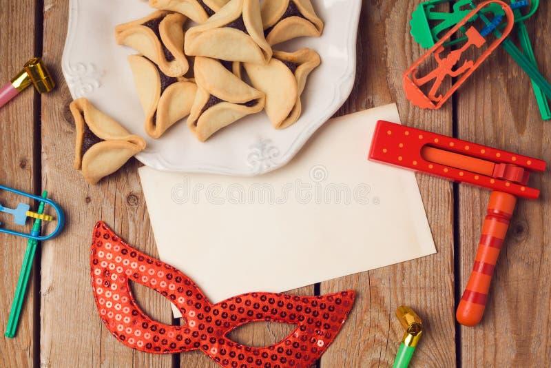 普珥节与贺卡的假日概念和hamantaschen在木背景的曲奇饼 库存照片