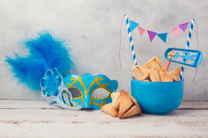 普珥节庆祝概念与hamantaschen曲奇饼和狂欢节面具 免版税库存照片