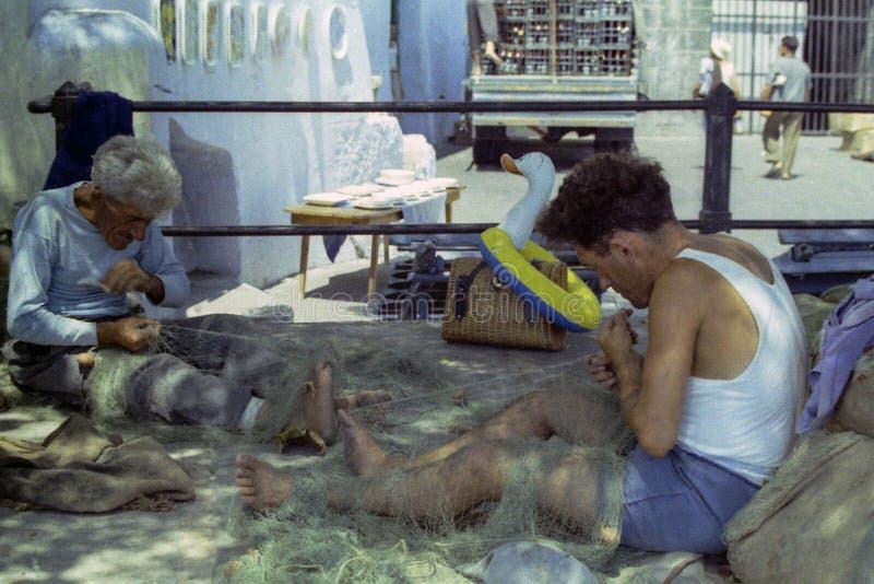 普罗奇达,意大利,1972年-两位渔夫修理他们的有技巧和经验的鱼网 库存图片