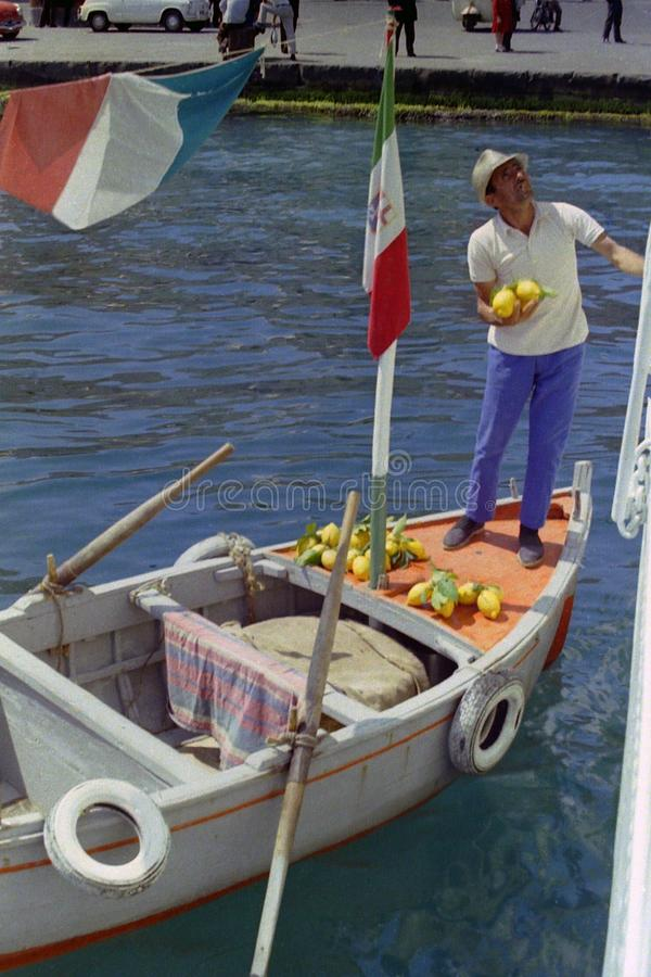 普罗奇达,意大利,1974年-船员卖普罗奇达柠檬给在口岸停住的轮渡的游人直接地乘他的划艇, 库存照片