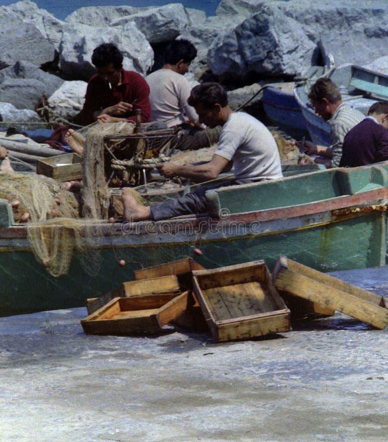 普罗奇达,意大利,1979年-有些渔夫修理他们的网耐心地技巧和并且烘干在普罗奇达太阳的有些鱼箱子 库存图片