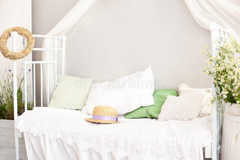 普罗旺斯,土气样式 与戴西花的花瓶桶在明亮,舒适卧室内部 白色墙壁,减速火箭的床,草帽 免版税库存照片